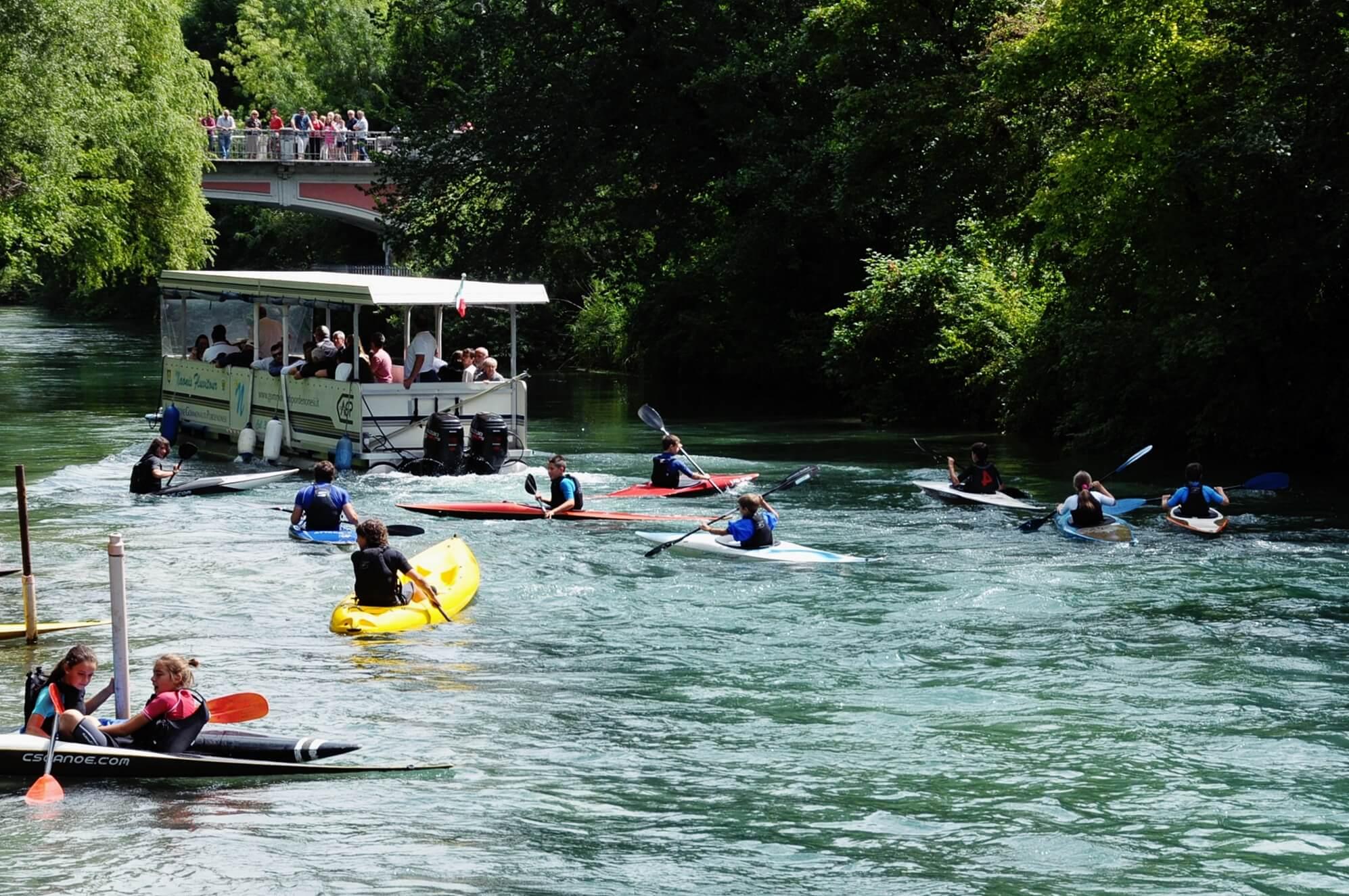 Nella foto bambini che fanno lezione di canoa sul fiume Noncello di Pordenone e persone che navigano sul battello
